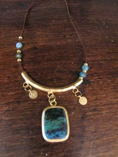 necklace with golden medals and green/blue stone