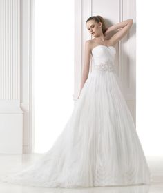 Organza princess dress with gemstone embroidery appliqués. Draped strapless bodice with gemstone embroidery appliqués at the waist. Fantasy tulle and organza skirt.