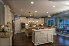 Three white pendant lights illuminate the center island in this open kitchen and dining area. The Avalon model from Pulte Homes at Scotts Creek. Mount Pleasant, SC.