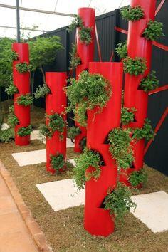Canos de PVC com 30cm de diâmetro, pintados de vermelho e adaptados para conter vasos internos dão personalidade ao jardim
