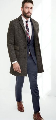 Pairing a grey herringbone overcoat with navy trousers will create a powerful and confident silhouette. Mix things up by wearing burgundy leather brogues.  Shop this look for $688:  http://lookastic.com/men/looks/blazer-and-dress-pants-and-overcoat-and-dress-shirt-and-tie-and-brogues/741  — Navy Blazer  — Navy Dress Pants  — Grey Herringbone Overcoat  — White Dress Shirt  — White and Red and Navy Tie  — Burgundy Leather Brogues
