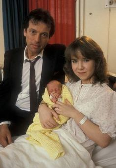 Den Watts, Michelle Flower and baby Vicki.  Played by Leslie Grantham and Susan Tully.