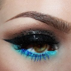 beautiful eyeshadow smokey eye, with a pop of blue and teal eyeliner. Arched eyebrows, cat eye, false eyelashes, makeup look
