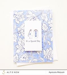 Agnieszka started with floral images from the Persian Motifs set stamped in dark blue. Next She used a blue marker to fill in the spaces between flowers and added some delicate blue splatters here and there. To finish, She added a white panel with a stamped sentiment and die cut numbers. www.altenew.com