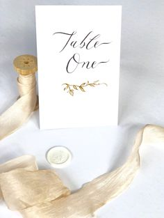 Dove gray calligraphy and delicate leaf motif. Table numbers for elegant weddings