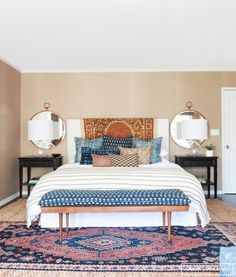 A symmetrical bedroom with round mirrors over the nightstands