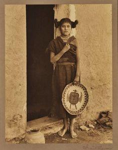 Hopi girl holding a plate basket at Oraibi Village (aka Third Mesa) in Arizona - circa 1890