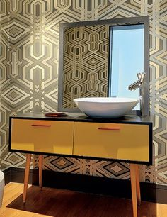 O móvel dos anos 1950 foi transformado em gabinete do lavabo, apenas com uma furação para cuba e misturador. O papel de parede com tons de dourado completa o ar retrô. Projeto das arquitetas Andrea Reis e Adriana Khalifeh