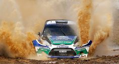 Petter Solberg and his co-driver Chris Patterson plough their Ford Fiesta RS WRC through a puddle during the Portugal FIA World Rally Championship third stage  Photograph: Francisco Seco/AP