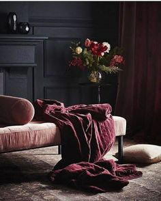 a pink velvet sofa draped with a burgundy throw - dark interiors with panelling