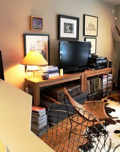 Mature, masculine living room. Cow's hide, leather chair, really cool wood console. Also like the frames behind the TV and the stacked leather suitcases in that space under the console