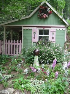 little pink and green cottage..looks like something out of a fairy tale..including the little front porch..