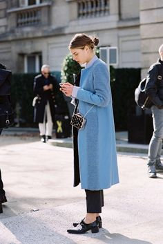 pastel blue coat, black trousers with low heel shoes, small black bag and simple hair // vanessa jackman