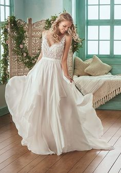 Pretty, flowy A-line bridal gown with a flattering v-neckline. Gorgeous allencon lace and beaded bodice. An iridescent chiffon skirt with light-weight cascading ruffles. This wedding dress is completed with a sweep/tiffany train.