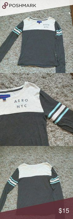 Aeropostale, long sleeve, grey shirt. This shirt is so soft and comfy! It's grey on the bottom and white in the shoulders. The white is see through just a warning. The logo is on the chest to one side and the sleeves are striped white and blue. It's in great condition! It was only worn a few times! It didn't fit my sister right. Aeropostale Tops Tees - Long Sleeve