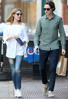 Daytime look: The socialite chose a loose-fitting white top that showed off her decolletage and featured knotted sleeve; pictured with a friend