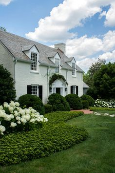 green and white landscaping + painted white brick house. classic and lovely!
