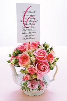 DIY: Write the table number and guests' names on a piece of card, then glue it to a length of dowling. Fill a vintage teapot with roses and stand the table-number card in the middle.