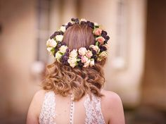 A floral crown designed for a bride or bridesmaid. This piece contains dark purple berries and pink roses.