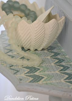 Vintage white chevron bowl with sea glass beads are displayed on a transformed mirror.  Before And After Coastal Style Mirror - Dandelion Patina
