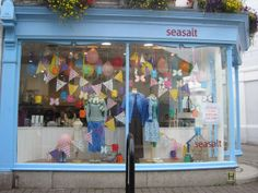 Summer window display with bunting and balloons in Seasalt Falmouth- like the banners