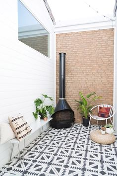 With a little help from these freshly patterned cement tiles, this petite patio spotted on The Glitter Guide draws your eye in and the clever use of a refurbished mid-century fireplace is the perfect antidote for chilly nights.