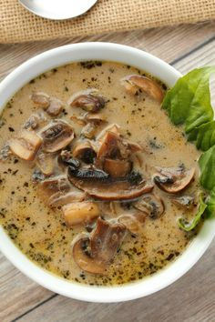 Vegan Cream of Mushroom Soup in a white bowl with fresh basil leaves.