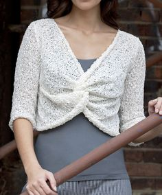 Free Knitting Pattern for Twist Front Top - Cute cropped pullover is knit in stockinette and seed stitch and gets it texture from the recommended yarn. This may only be free for a limited time. Designed by Coralie Meslin for Tahki Stacy Charles. Sizes Small (Medium, Large, XL)