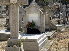 Black cat sleeping on a grave in the Old Torrero Cemetery in Saragossa, Spain