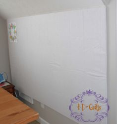 Design wall for under $20 using 6×8 piece of insulation foam core board from Home Depot, a rectangular vinyl tablecloth with flannel backing (from Party City), and hung with 3M strips.