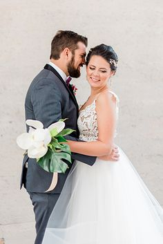 Tropical styled shoot at the 1912 bride tulle ball gown with lace bodice and thin straps with open back design and crystal headpiece with groom charcoal grey tuxedo with white dress shirt and matching vest with purple bow tie and matching pocket square with bright pink tropical floral boutonniere