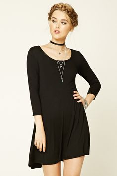 A soft knit trapeze dress featuring a scoop neckline, 3/4 sleeves, and a flowy hem.