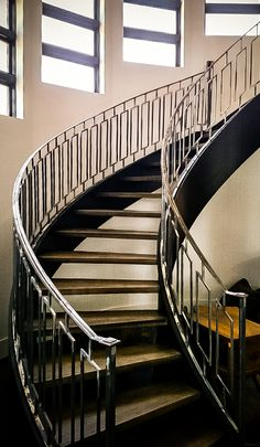 GREAT RAILING AND SETS A NICE OVERALL TONE  IF WE NEED TO SPEND $ ON STAIRS I LIKE THESE  MAYBE ITS CHEAPER TO HIDE THE STEPS....AND USE LESS SPACE Modern curved staircase with hand forged wrought iron railing.