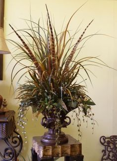 An abundant gathering of grasses in several sizes is displayed in an exotic dark brown pedestal vase created with 3 elephant heads.