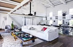 une ancienne usine transformée en maison loft tapis berbere noir et blanc losange intérieur décoration canapé blanc tissu trois places déco loft inpiration tabla basse diy roue roulettes indus industriel style