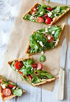 Delicious looking pizza with cherry tomatoes, rocket, feta and basil