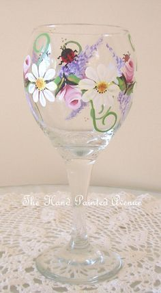 ****** Lucky Ladybug Wine Glass ******* This hand painted wine glass features a cluster of garden flowers surrounding the glass with