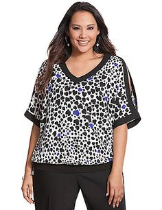 Fun-loving print block top works a little sass into your wardrobe with cold shoulders and an alluring V-neckline. Breezy woven construction comes together with a knit banded bottom to define the fit.  lanebryant.com