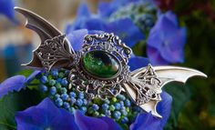 Barrette à cheveux (8cm de largeur) composée de plusieurs estampes en métal vieilli. Deux ailes enserrent un cabochon de verre qui contient des tâches de vert, noir et dorés qui lui donnent un côté...