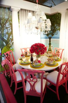 Traditional Chippendale chairs painted bright candy pink in this dining room...