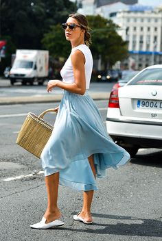 White tank top, a baby blue midi skirt, white mules, cat eye sunglasses and a straw tote.
