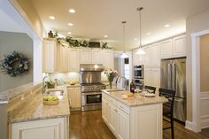 White cabinets with hardware, Kitchen with granite countertops and hardwood floors, island with seating, and great lighting.