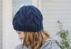 the skalbagge cabled hat is a free knitting pattern for a beginner-friendly hat with alternating cables that decrease into the crown.