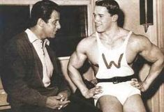 ILYKS.COM - Arnold Schwarzenegger at age 15 or 16 happy and talking to unknown person while sitting down with muscles clearly developed already A young winner