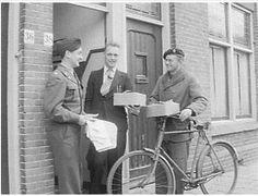 Een illegale Nederlandse helper wordt door twee geallieerde soldaten bedankt om zijn hulp aan neergestorte piloten. Hij krijgt een fiets en textielgoederen cadeau. November 1945. Bron: Nationaal Archief.