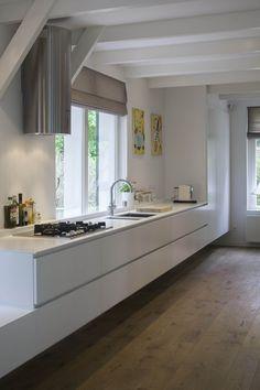 Molen in Muiden. Renovatie en verbouwing van een woning in het groen. Ontwerp en interieurontwerp door BO6 architecten. De zwevende witte keuken is op maat gemaakt.