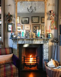 Beautiful fireplace, love the fairy lights and the hanging puppets. Eclectic design.