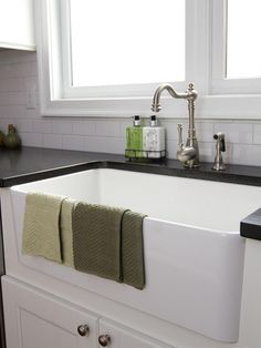 AFTER: A deep farmhouse sink with a simple modern faucet makes washing dishes a breeze, and the black countertops pop against the white subway tile backsplash.