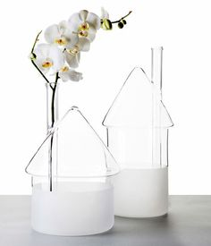 """flood"" is a set of two house-like vases by david raffoul, meant to reflect houses flooded and damaged by storms and from that, a flower grew through its chimney."