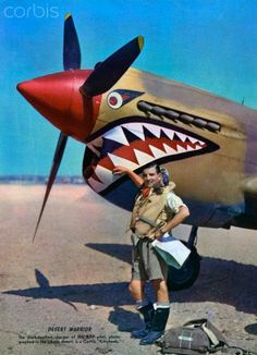 """Desert Warrior"" – an RAF pilot stands next to his Curtiss ""Kittyhawk"" in the Libyan desert in 1942. The aircraft is painted with shark-toothed nose art. Screen print, 1942."